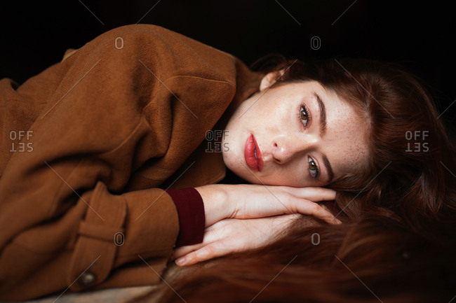 Charming thoughtful woman in brown coat lying on hands dreaming while looking away