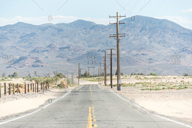Rural highway at dusty field with power line and remote mountain range in USA