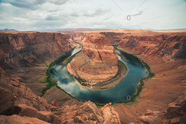 Scenic colorful rocky gorge with smooth lake in center on cloudy day in Horseshoe Bend, Arizona, USA