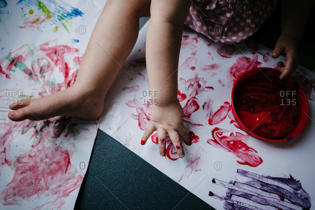 A close up of a child's finger painting red paint on a large piece of white paper