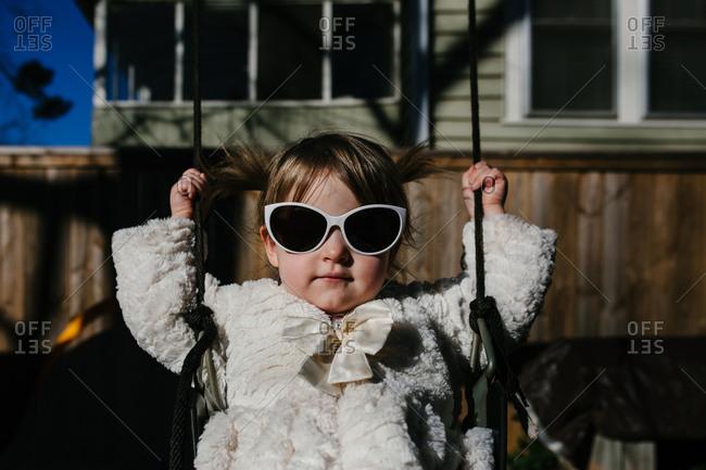 Child wearing sunglasses swinging on a swing