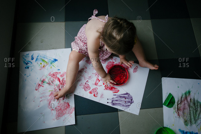 A girl sits on the ground and finger-paints on large pieces of white paper