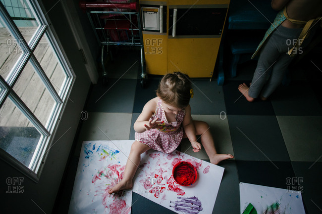 A girl sits on the ground and finger-paints on large pieces of white paper with another child in the background