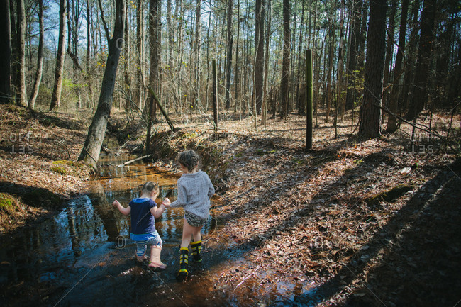 Two sisters hold hands while walking through a creek in the woods