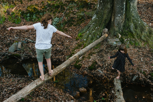 Two girls balance on logs over a creek