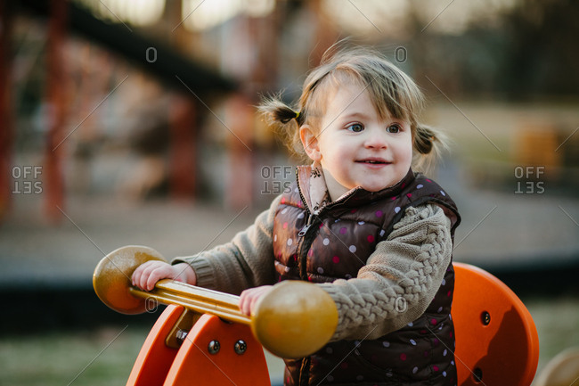 Girl smiles while playing on playground equipment
