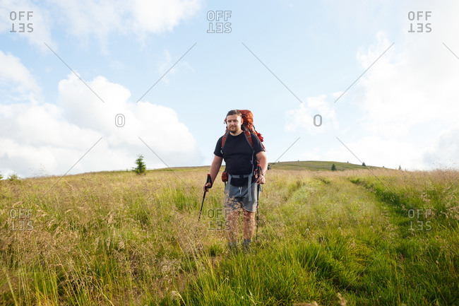 a guy in a black t-shirt with a red backpack and trekking poles