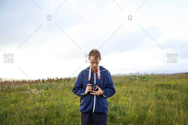 blond guy in a blue jacket with a camera in his hands among mountains