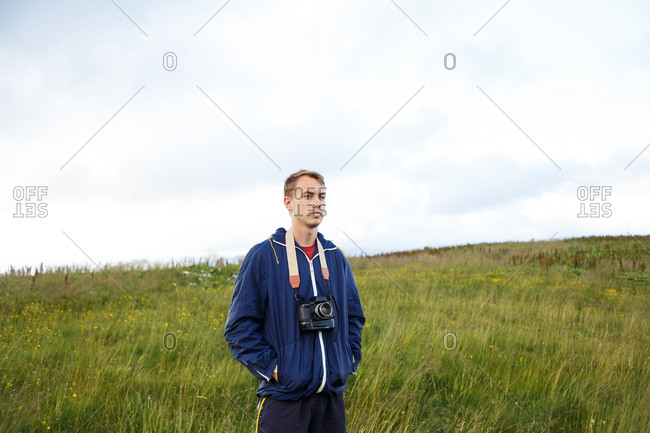 guy in a blue jacket with a camera in the middle of the mountains