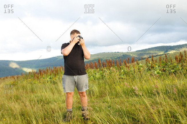 guy in black t-shirt takes pictures of Carpathians landscapes