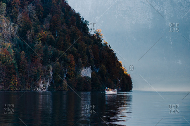 boat through the blue waters of Lake Königsee surrounded by mountains