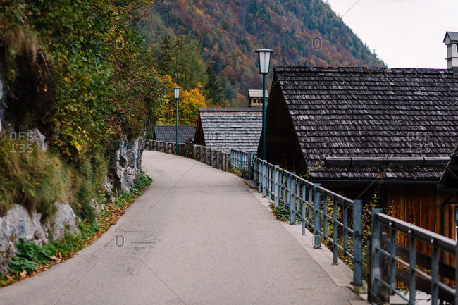 empty street surrounded by wooden houses and Alpine mountains