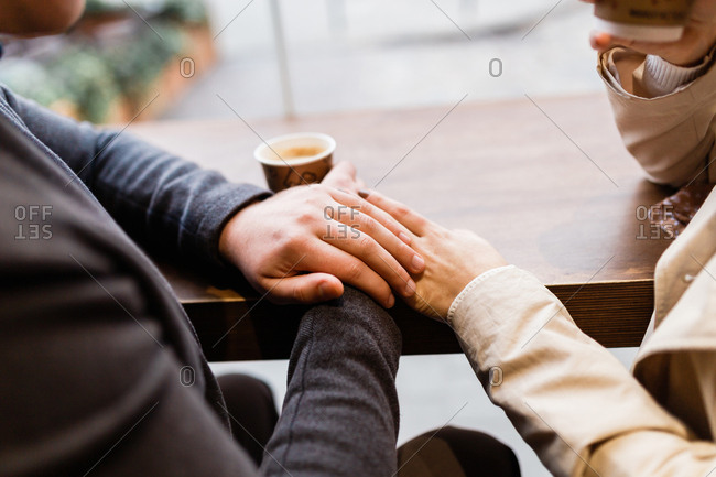 couple holding hands enjoying coffee by the window