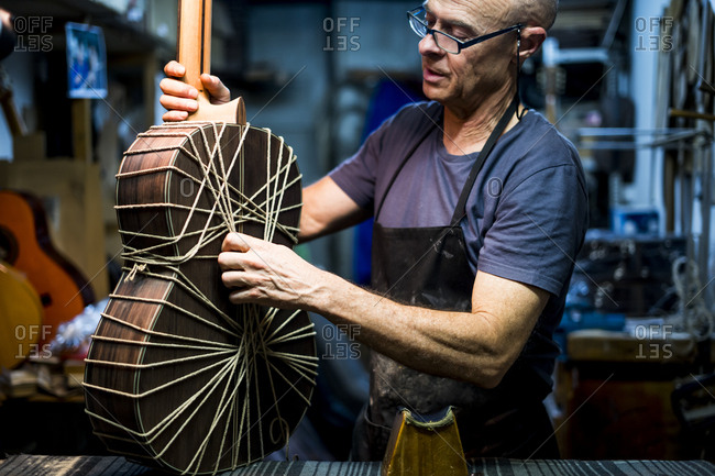 Luthier man making guitars in artisan workshop in Spain.