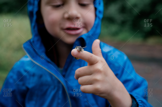 young boy standing in the rain smiling with a snail on his finger