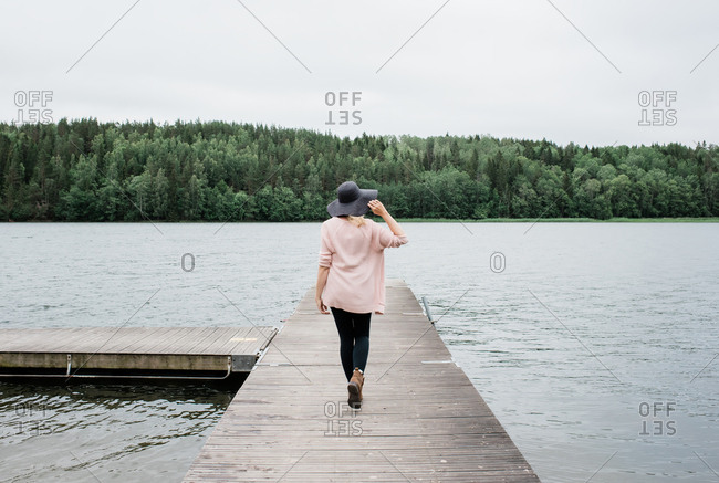 woman with a hat on walking along a jetty by the sea enjoying the view