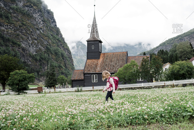 girl backpacking outside a beautiful church & fjord in Fläm, Norway