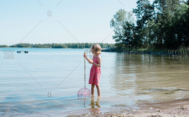 blonde girl fishing in the sea eating an apple on vacation in summer
