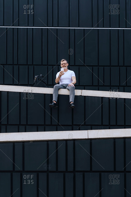 mature bearded businessman with smartphone sitting on wall while looking camera