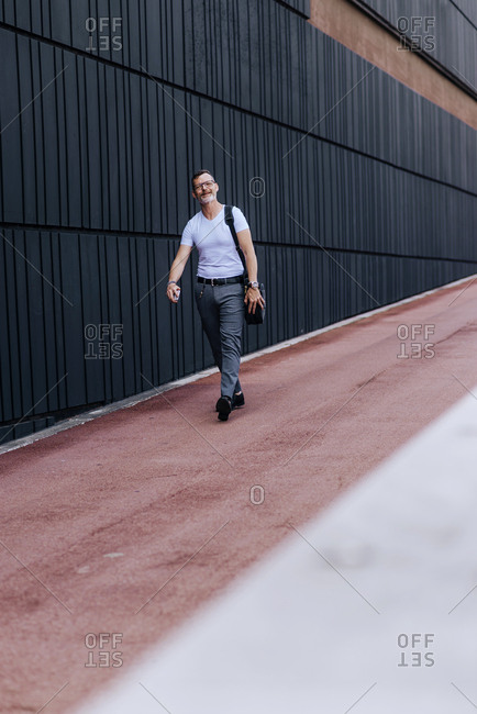 Mature bearded businessman with shoulder bag in the city