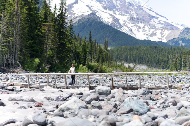 Hiker is standing on the log bridge at Mt Rainier National Park