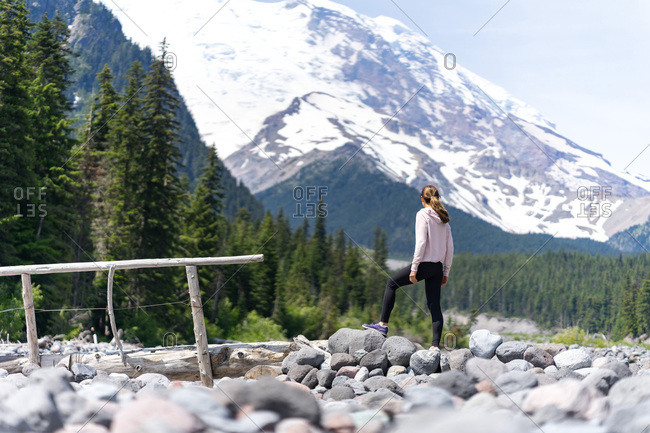 Woman hiker is thinking about hiking to the top of the mountain