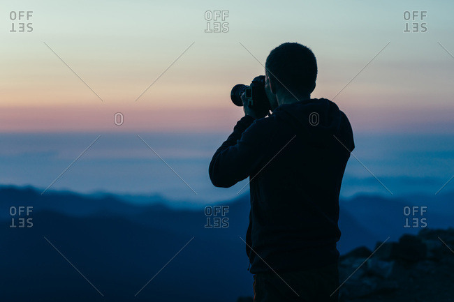 Man taking picture of purple sunset in Washington's National ParkMan t