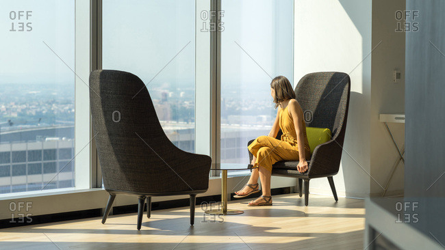 Woman in yellow suit looking outside of the giant window in New York