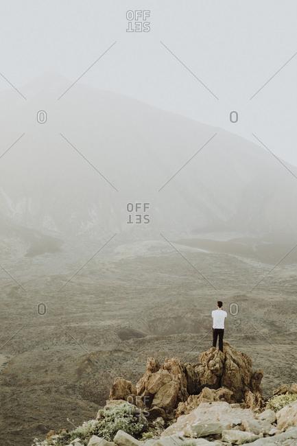 A man takes a photo of Mount Teide on a hazy day