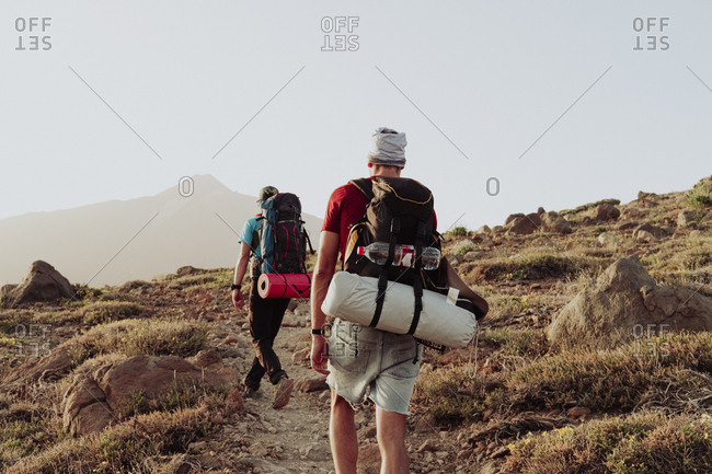 Two men walk on trail with camping gear and Mount Teide in background