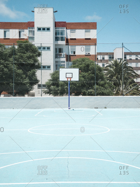 Basketball goal on blue court against blue sky and colorful buildings