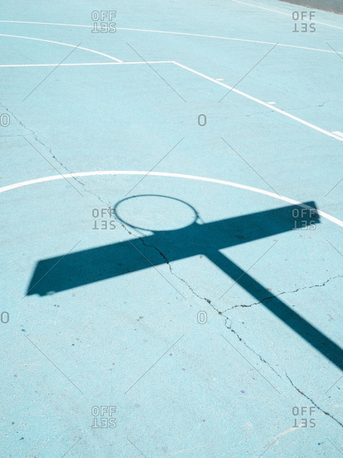 Basketball hoop shadow and white lines on blue court surface