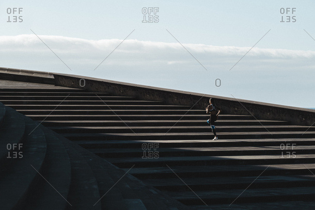 Pulled back of woman running on stairs with blue sky in background