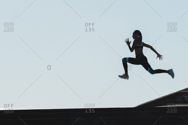 Silhouette of female athlete jumping against blue sky