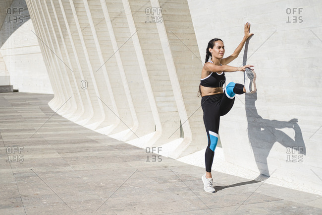 Full body of female athlete stretching legs against concrete wall