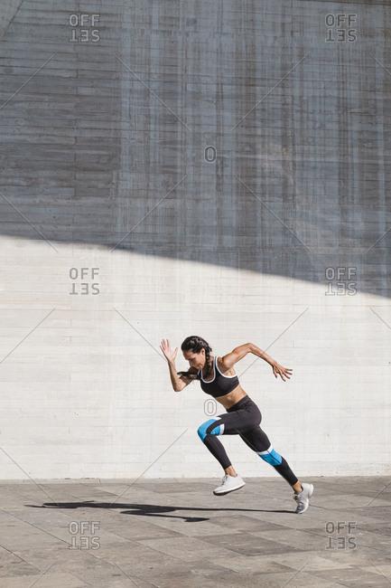 Female athlete running on concrete vertical