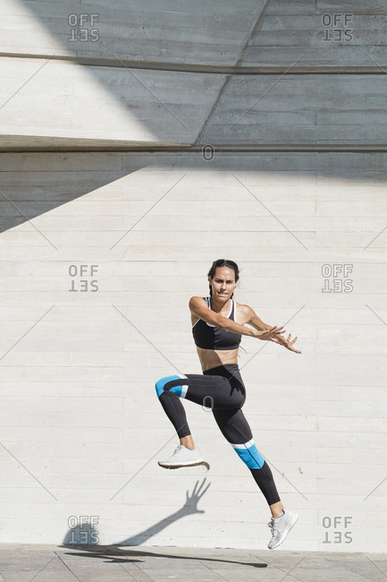 Full body of female athlete in sportswear jumping on concrete