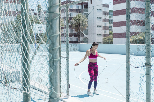 Colorful image of female athlete skipping with jumping rope on court
