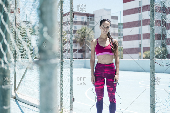 Colorful image of female athlete posing with jumping rope on court