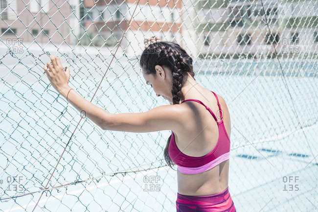 Upper body of female athlete leaning on court fence while resting