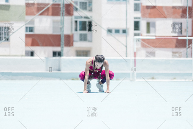 Colorful image of full body of female athlete resting on court