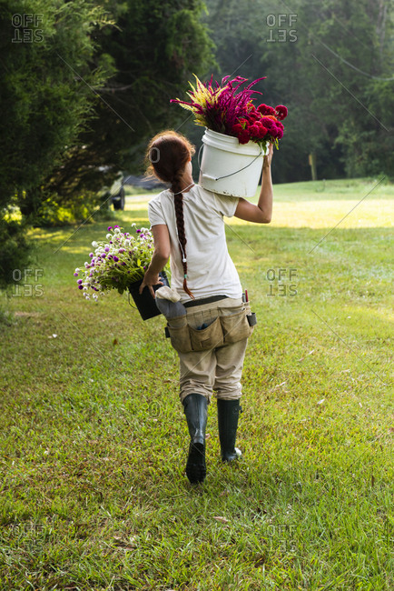 Young woman holds two buckets of freshly-cut flowers in a green filed