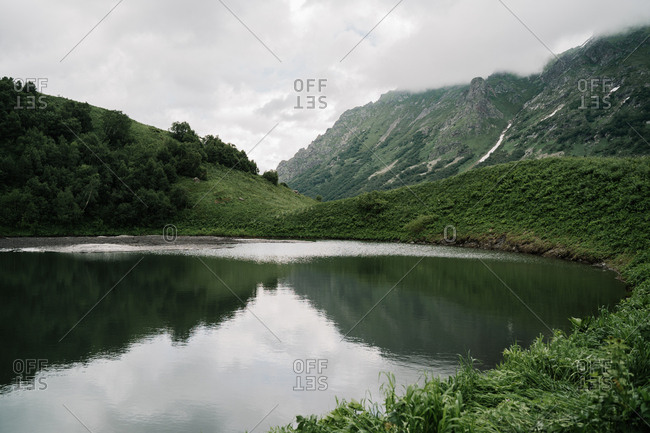 Cold summer lake in the mountains with snow