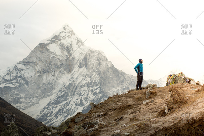 A man stands in front of Ama Dablam at the Everest Memorial Park.