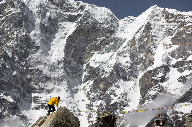A man scrambles under the mountains of the Himalayas.