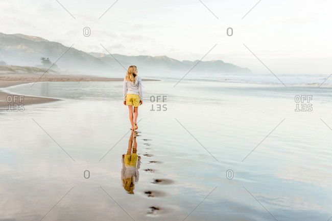 Back view of girl walking at beach