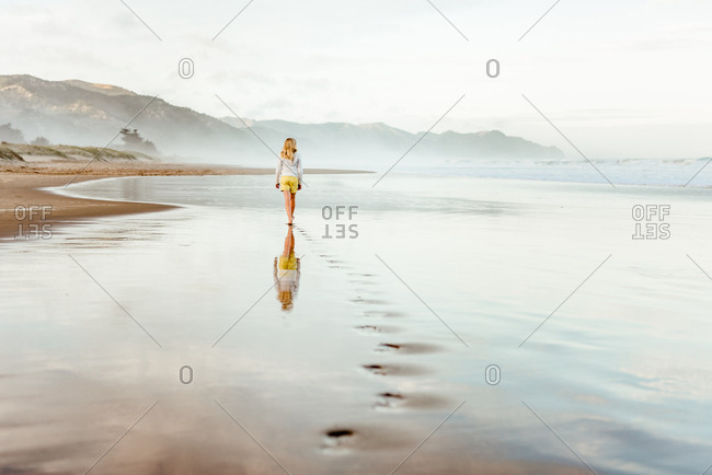 Preteen girl waling on beach in New Zealand