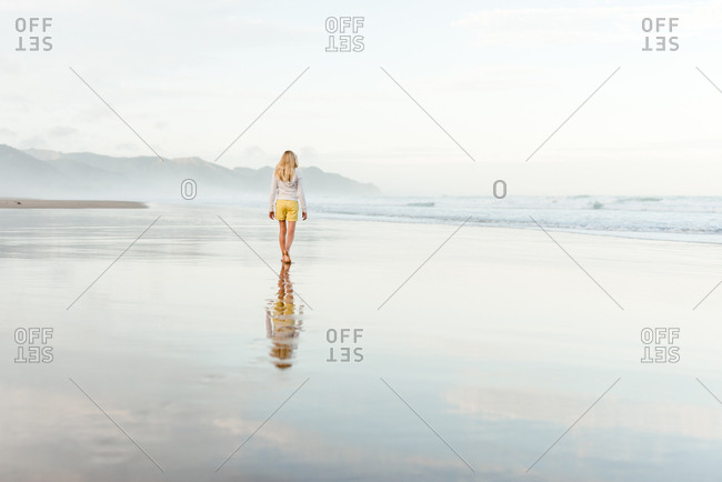 Young female walking on a beach with reflection