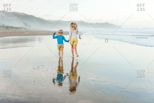 Sister and brother running together at a beach