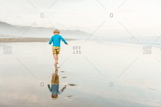 Back view of child running on a beach with footprints
